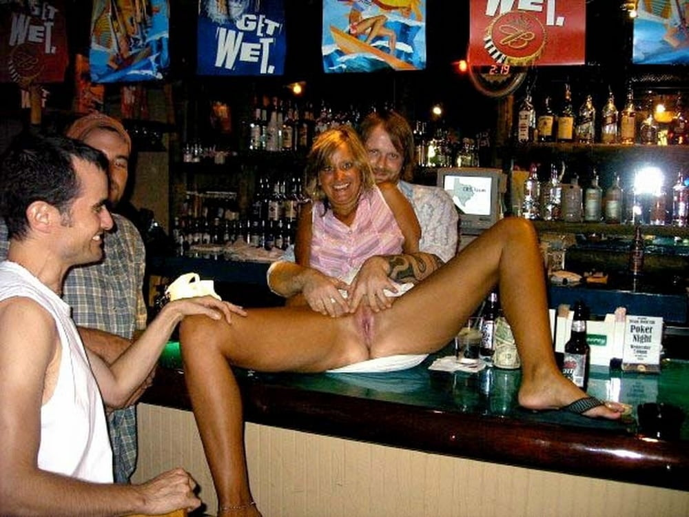 Blonde chick removes vintage lingerie and nylons to pose nude inside a bar